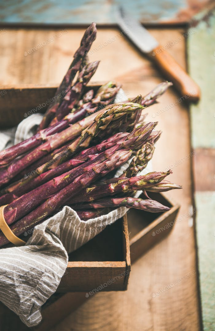 Fresh raw uncooked purple asparagus over rustic background