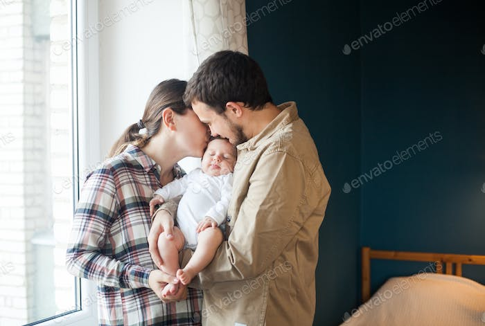 Happy young parents and baby together at home.