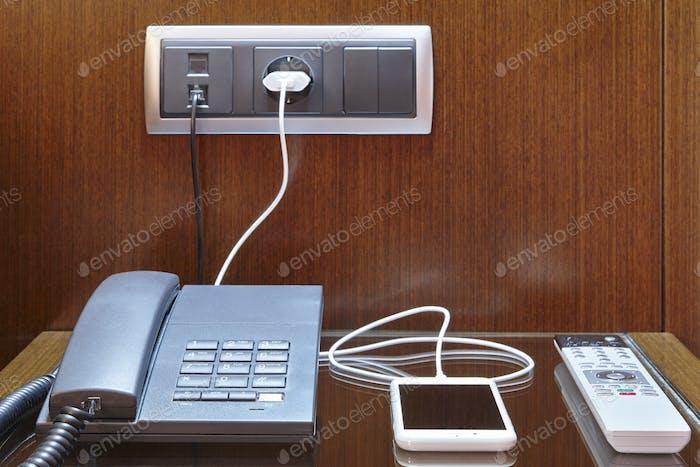 Loading smart phone. Hotel room desk. Travel business background. Equipment