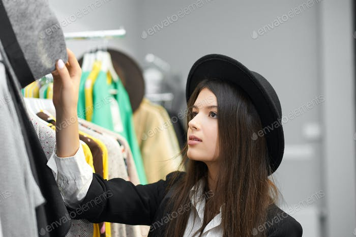 Pretty girl trying on black hats in clothing shop