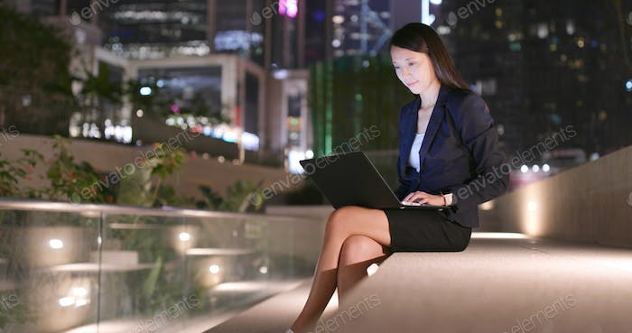 Business woman use of notebook computer at night