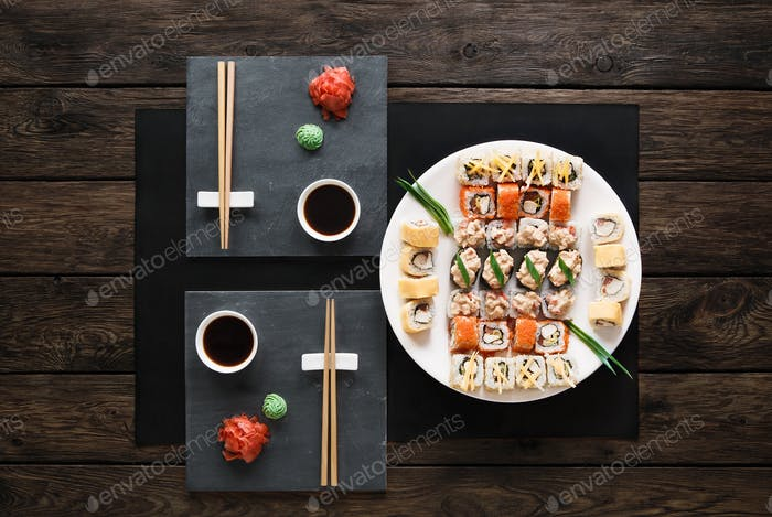 Set of sushi maki and rolls at black rustic wood.