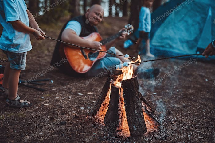Boy toasting marshmellow and his father playing guitar in forest