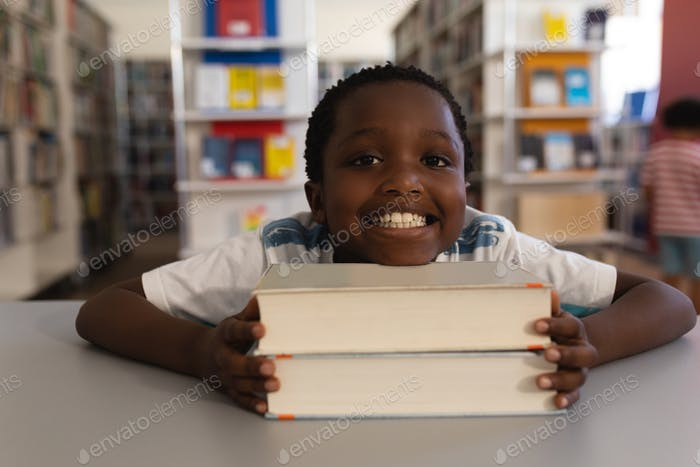 Schoolboy leaning his face on books and looking at camera on table in school library
