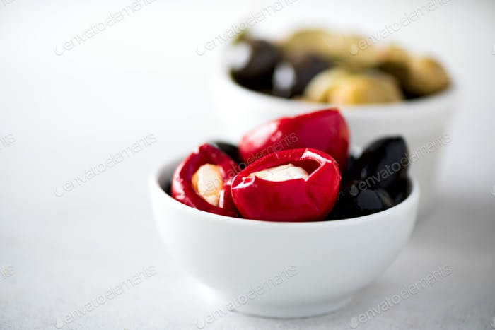 Olives and tomatoes with feta cheese in white bowls on grey background