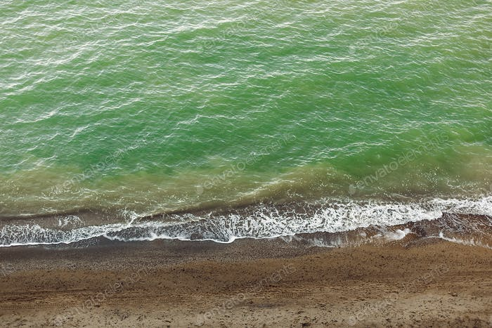 Beautiful top view of blue sea water  and waves from sandy cliff with grass