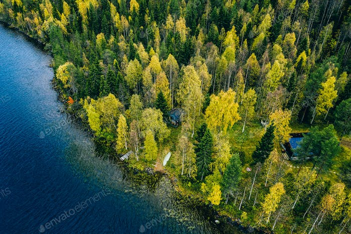 Aerial view of cottage in autumn colors forest by the blue lake in rural  Finland