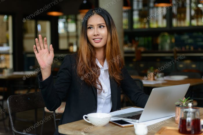 Happy young beautiful Asian businesswoman at the coffee shop
