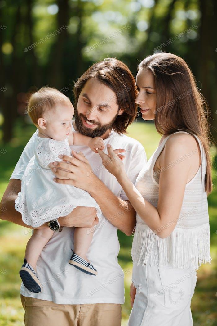 Jovens pais bonitos vestidos com roupas brancas estão segurando sua pequena filha encantadora no