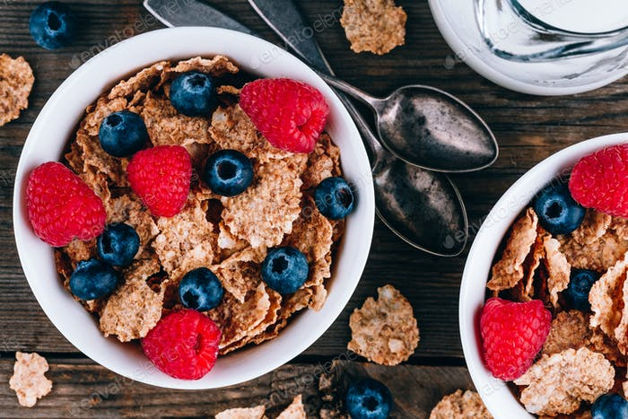 Vollkorn gesundes Getreide mit frischen Blaubeeren und Himbeeren zum Frühstück.