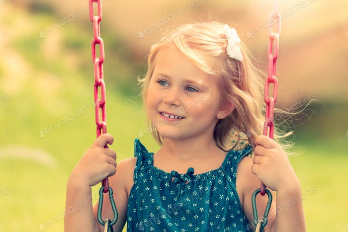 Little girl is riding on a swing