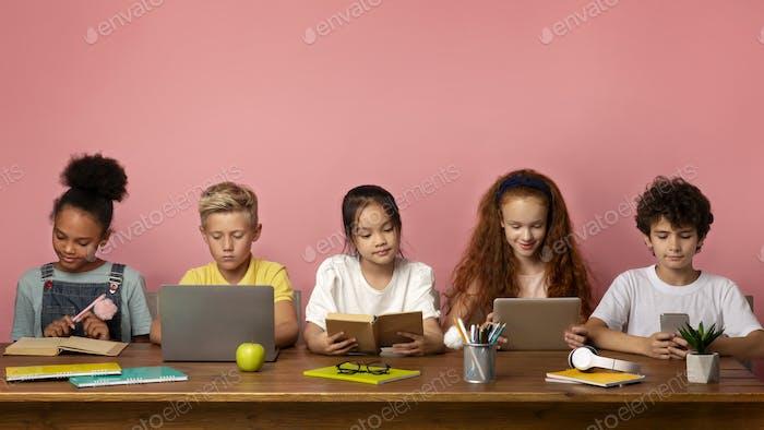 Multiethnische Kinder mit elektronisch Geräten und Büchern, die am Tisch über rosa Hintergrund studieren, kostenlos