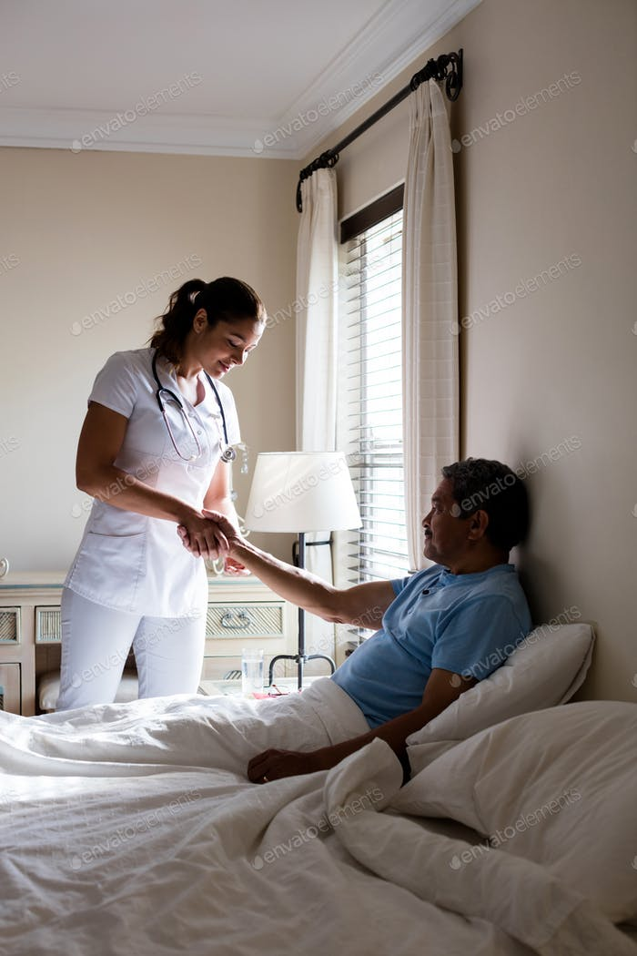 Female doctor examining senior patient in bedroom