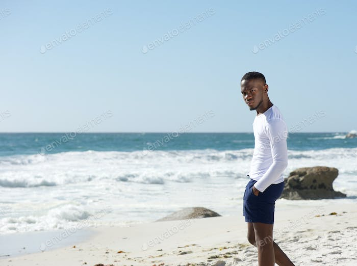Handsome young man standing alone at the beach
