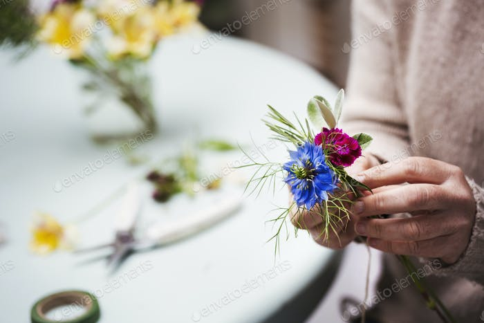A florist creating a small posy or buttonhole.