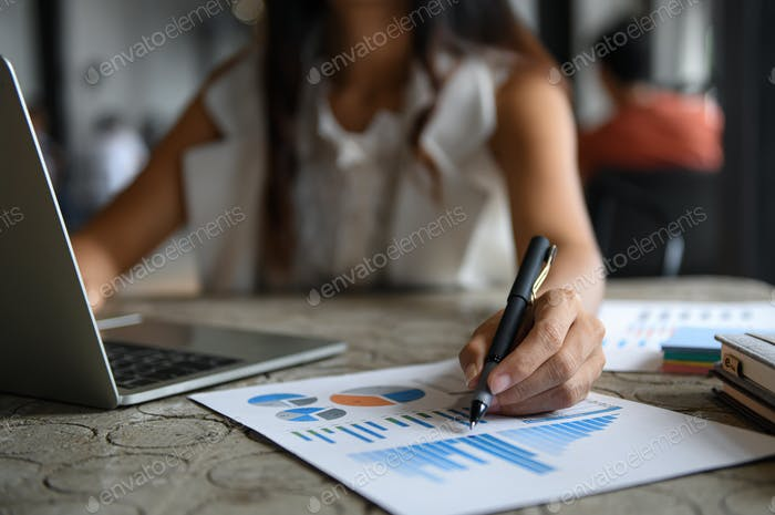Female businessmen are checking data graph and using laptop.