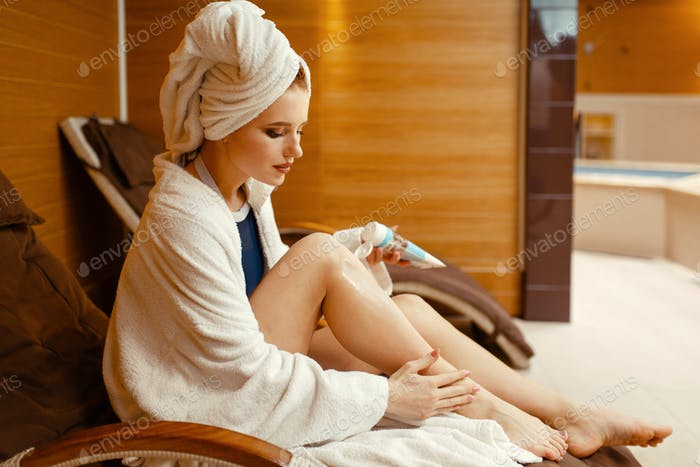 Sexy girl applying cream in spa chair, body care
