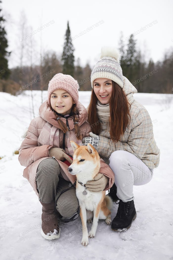 Portrait of Happy Family with Dog in Winter Park