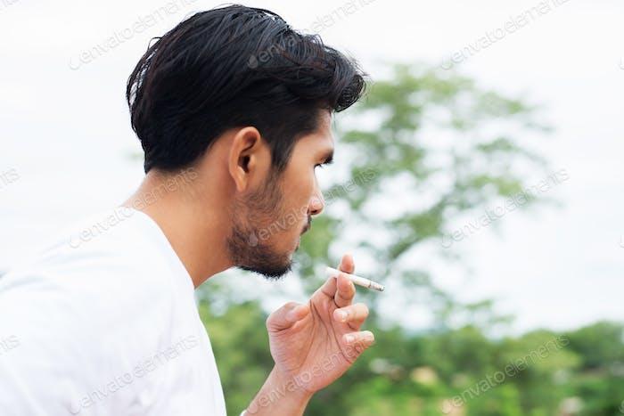Junger Hipstermann ruht sich aus, raucht Zigarette mit der Natur und frischer Brise.