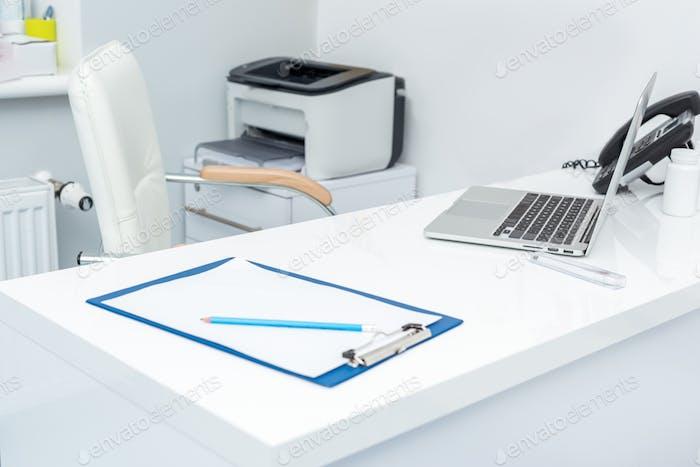Kinderarzt Arbeitsplatz mit Laptop und Zwischenablage in der modernen Klinik