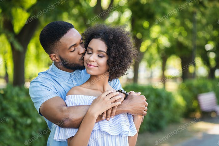 Portrait of young man kissing woman in cheek