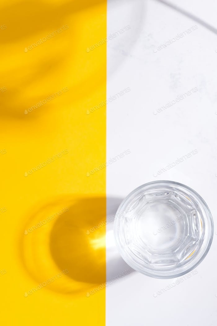 Top view of glass of fresh cold clean water on a duotone yellow white background with soft shadows