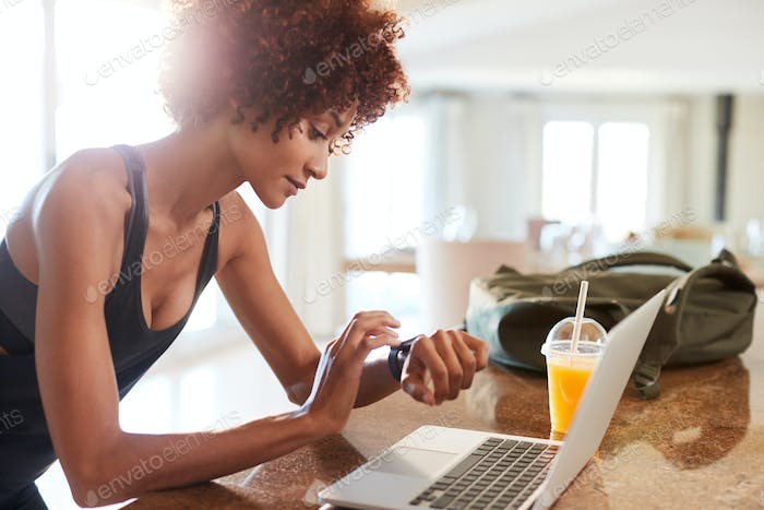 Millennial African American woman checking fitness app on watch and laptop after workout, side view