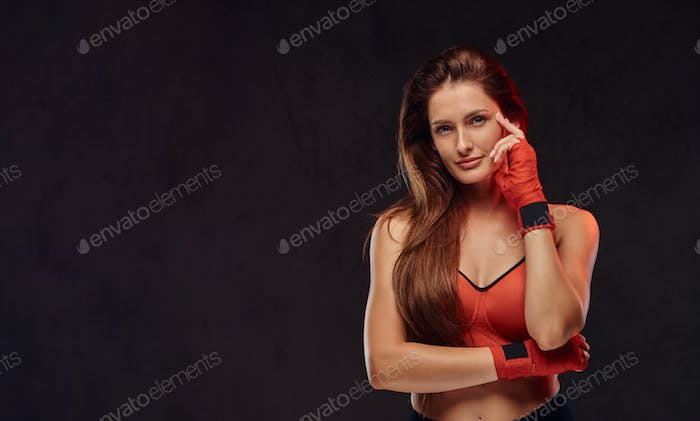 Beautiful brunette female boxer in sportswear. Isolated on dark textured background.