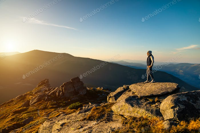 Young man on top of a mountain watching the sunset