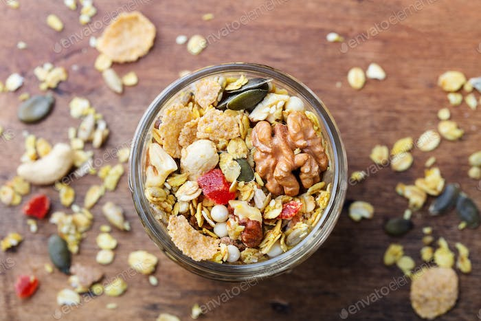 Granola, Muesli in Glass Jar. Organic Oats with Turmeric, Nuts, Fruits and Berries.