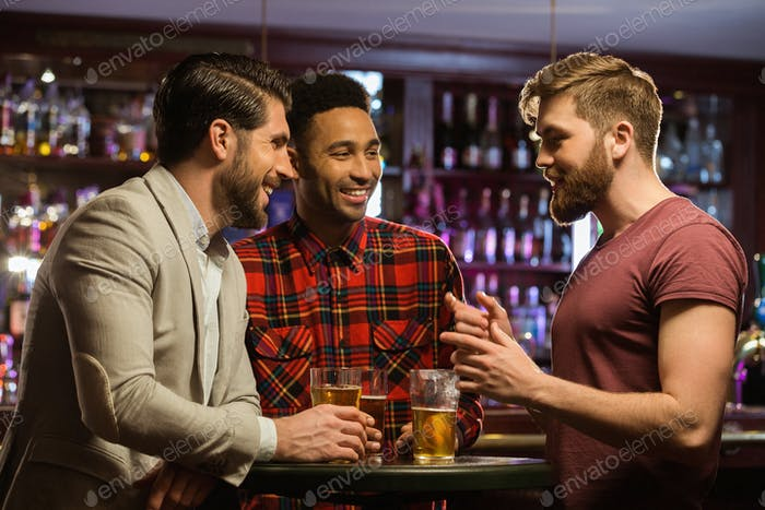 Young happy men drinking beer and talking in cafe