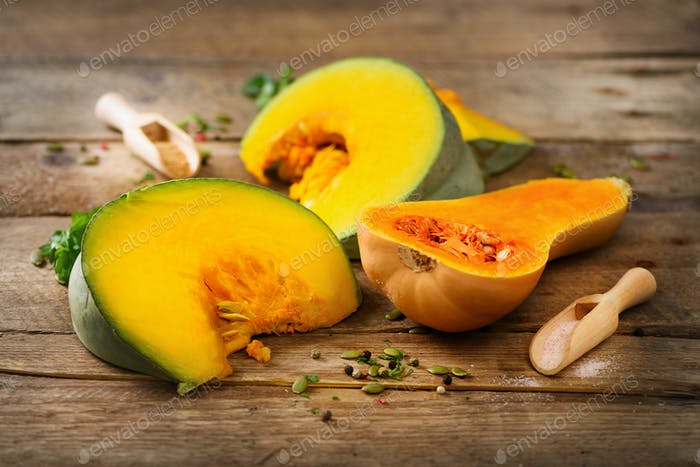 Cut ripe orange pumpkin with seeds and herbs on rustic wooden background. Vegetarian and raw organic