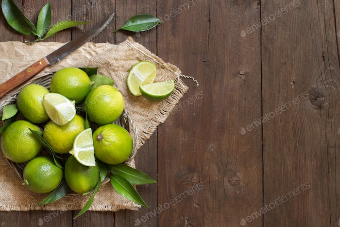Fresh limes with knife and leaves