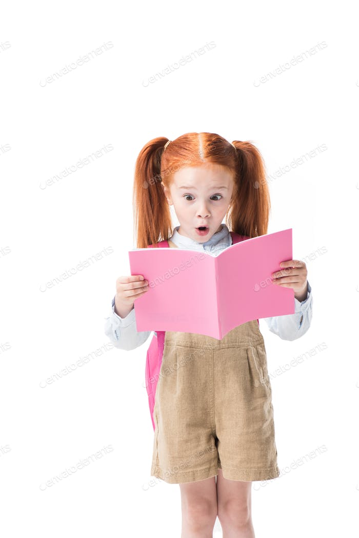 Adorable surprised redhead schoolgirl holding book isolated on white