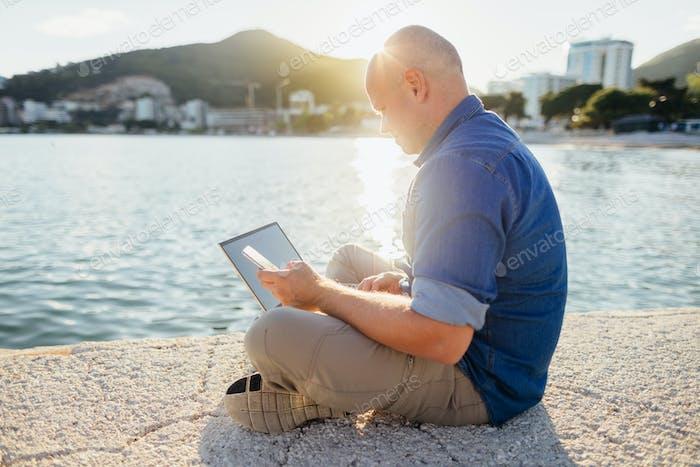 Mann mit Laptop am Meer
