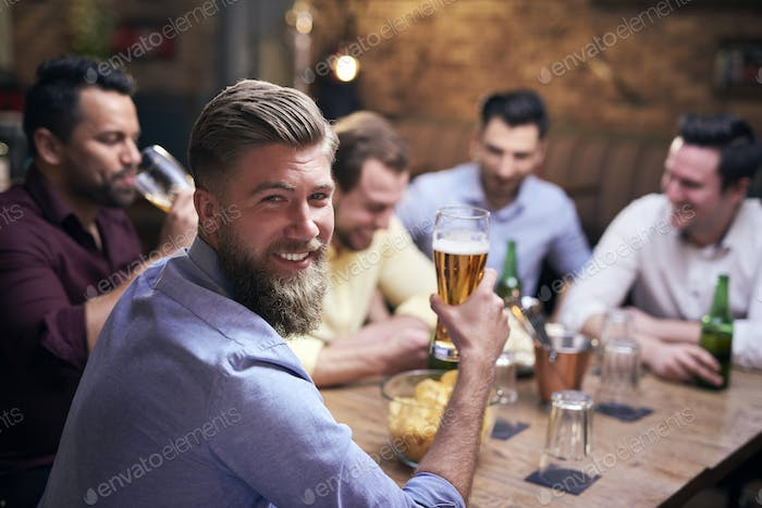 Man drinking beer in pub and friends in the background