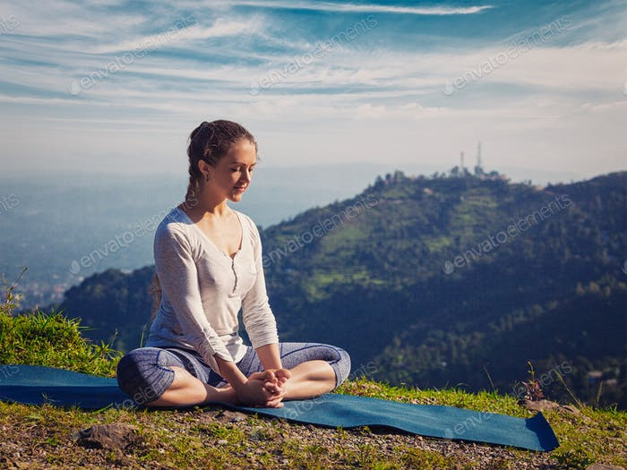 Sporty fit woman practices yoga asana Baddha Konasana outdoors