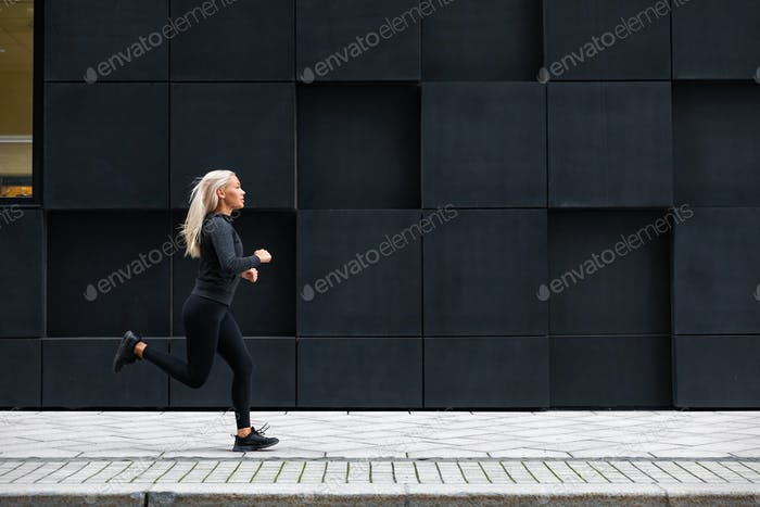 Woman running on the city street against modern city walls