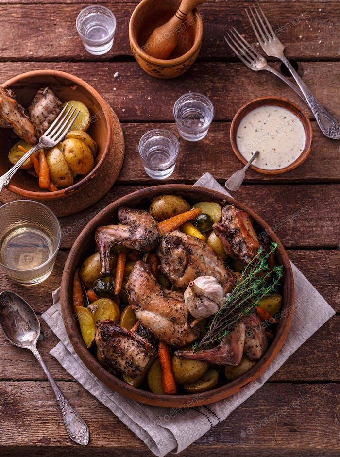 Kaninchen mit Kartoffeln und Karotten in einem Keramiktopf gebacken