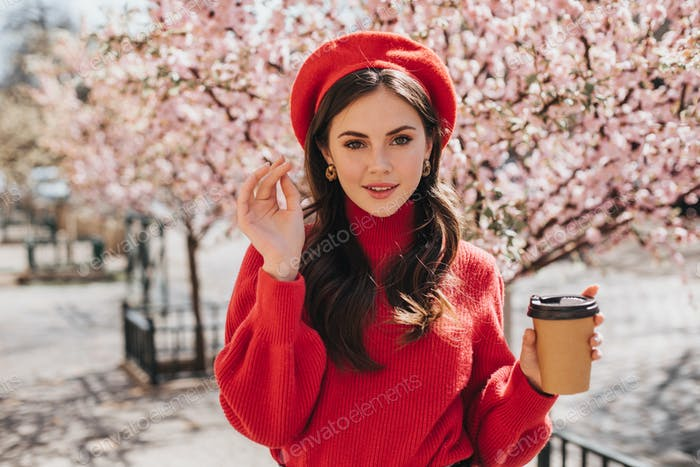 Attractive lady in red sweater walks along avenue with sakura and drinks coffee. Beautiful woman in