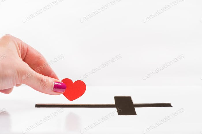 Close-up partial view of woman inserting red heart symbol into hole for donations in form of cross