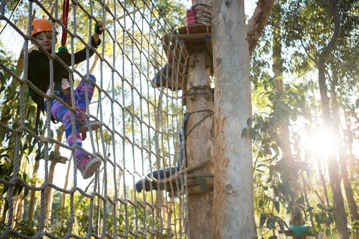 Little girl wearing helmet climbing on rope fence