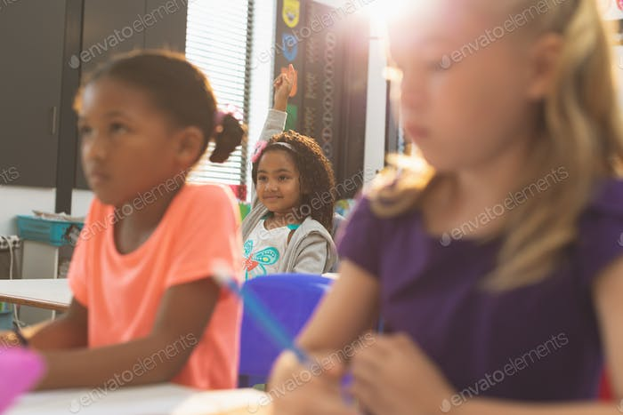 Schoolgirls sitting at desk in school and listening their teacher