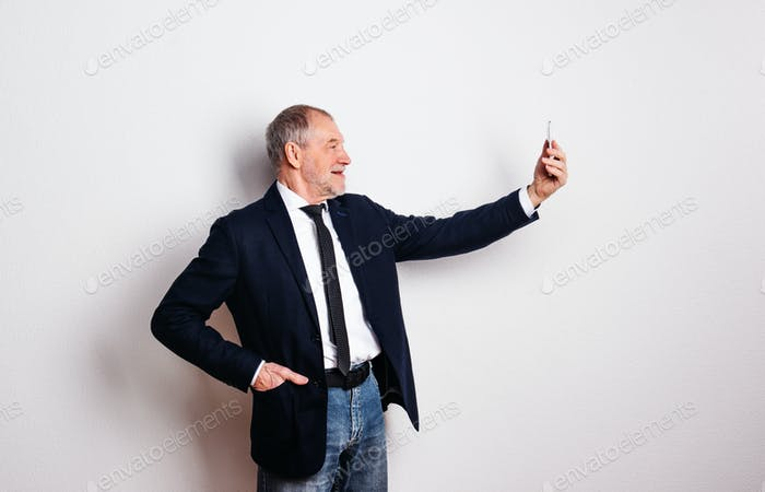 Portrait of a senior man with smartphone in a studio, taking selfie