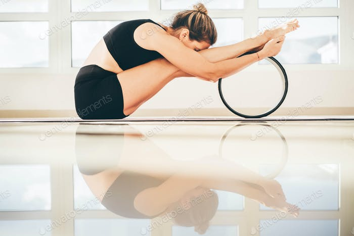 Sportive woman training using yoga wheel to build spine and back flexibility.