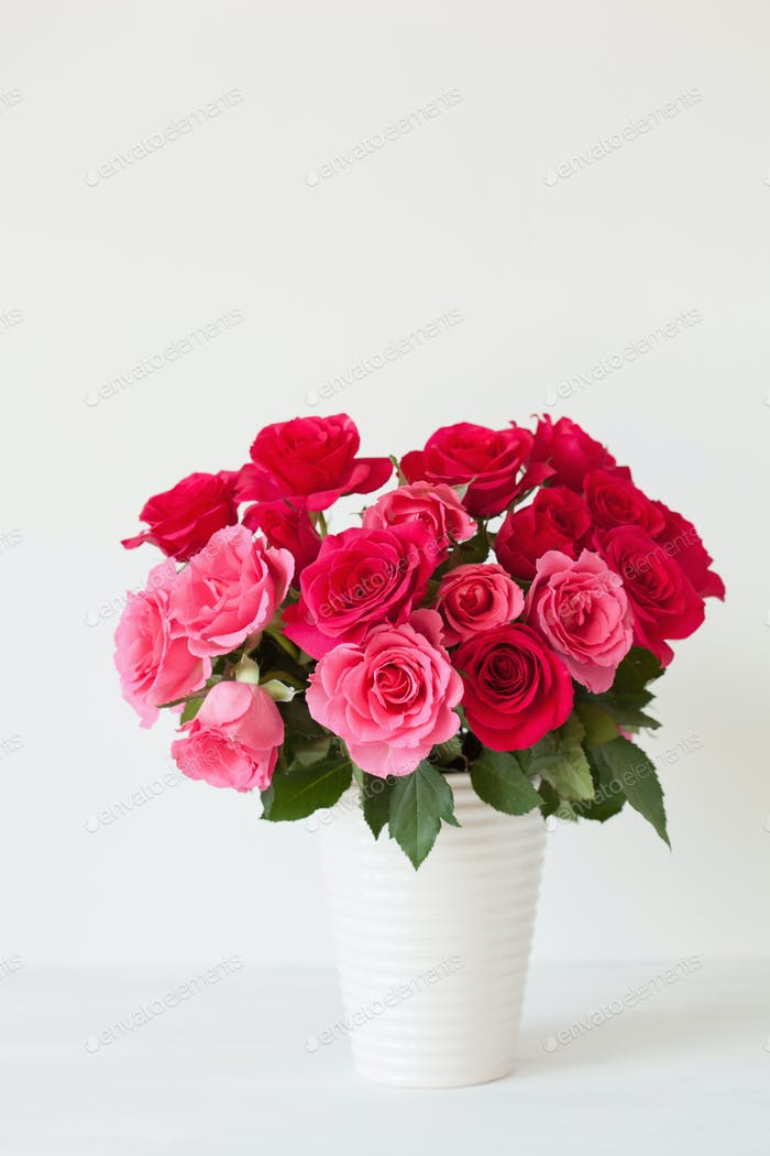 beautiful red rose flowers bouquet in vase over white