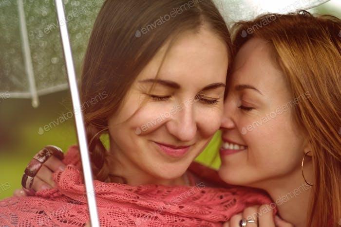 Two young beautiful women secret at summer green park