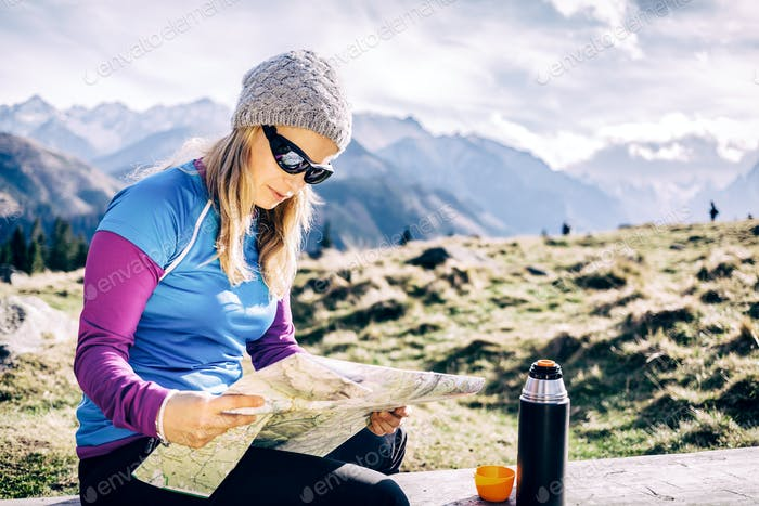 Woman checking map hiking in mountains