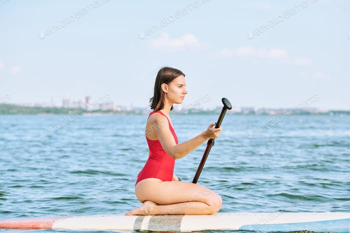 Young serene sportswoman in red swimsuit floating on water at summer resort
