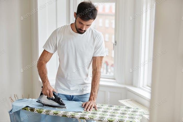 Concepto de limpieza y tareas domésticas. Trabajo duro marido guapo plancha ropa en tabla de planchar, hacer